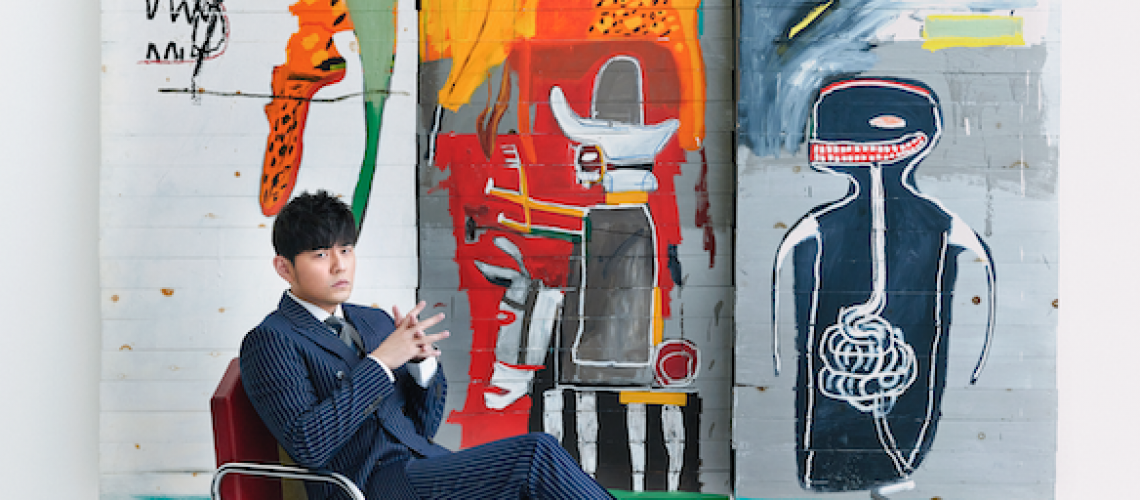 Jay Chou in front of Basquiat's Untitled (seated) (Photo courtesy of Sotheby's x Enviseam)